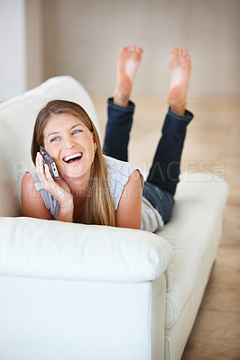 Buy stock photo Laughing young woman enjoying a phone conversation while lying on the sofa
