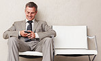Happy business man reading an SMS while waiting for someone