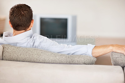 Middle aged man sitting in sofa while watching television