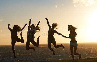 Buy stock photo Silhouette of a group of girlfriends on the beach having lots of fun jumping around