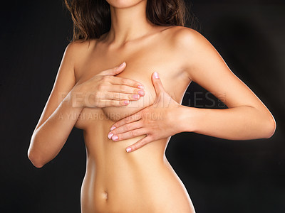 Buy stock photo Cropped studio shot of an unrecognizable young nude woman doing a self-breast examination while standing against a black background