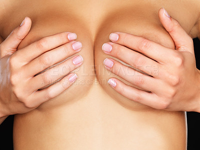 Buy stock photo Studio closeup of an unrecognizable woman's hands as she cups her breasts while standing against a black background