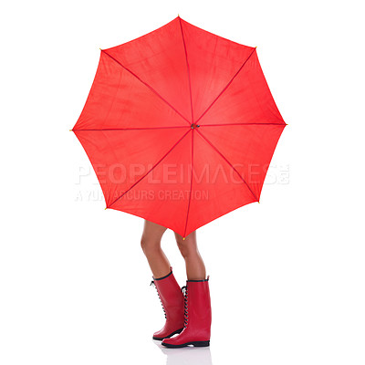 Buy stock photo Studio shot of an unrecognizable woman holding a red umbrella and wearing gumboots while standing against a white background