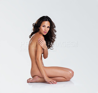 Buy stock photo Studio portrait of a attractive young nude woman seated on the floor and covering herself against a white background