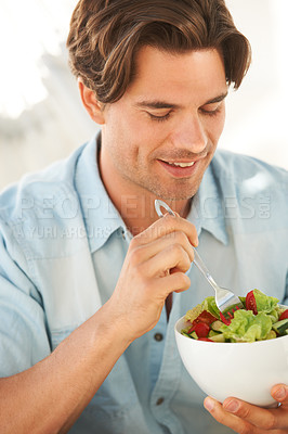 Buy stock photo A healthy young man eating a bowl of salad