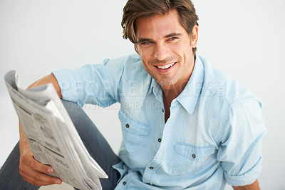 Buy stock photo A handsome young man sitting with a newspaper