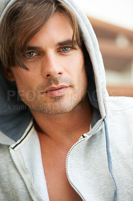 Buy stock photo Portrait of a tough looking young man wearing a hooded jumper