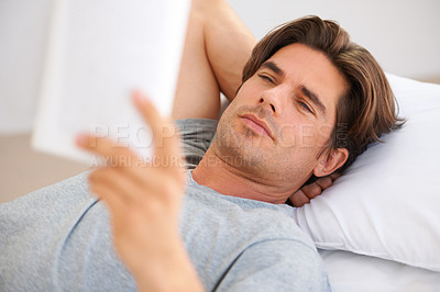 Buy stock photo A handsome young man reading a novel while lying on a bed