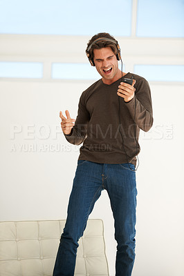 Buy stock photo A handsome young man dancing to the music on his mp3 player