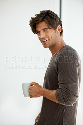 Buy stock photo A handsome young man standing at home and holding a cup of coffee
