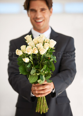 Buy stock photo Portrait of a handsome young man wearing a suit and holding a bunch of roses