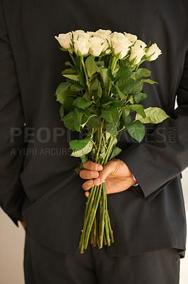 Buy stock photo Cropped image of a young man in a suit holding a bunch of roses behind his back