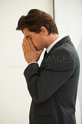 Buy stock photo Profile of a young businessman with his hands over his face and showing signs of stress