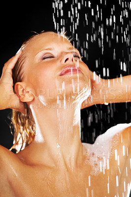 Buy stock photo Gorgeous young woman feeling the water drops on her face as she has a refreshing shower