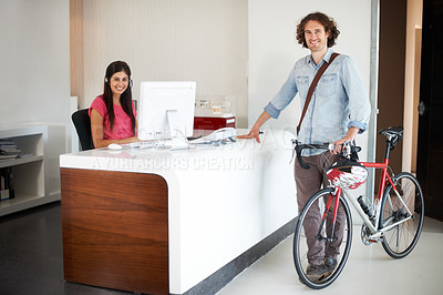 Buy stock photo Shot of a young bike messenger delivering mail to an office reception desk