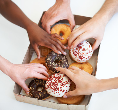 Buy stock photo High angle shot of a group of businesspeople grabbing doughnuts while in a meeting