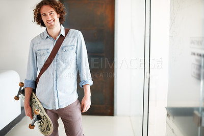 Buy stock photo Shot of a young businessman arriving at work with his skateboard