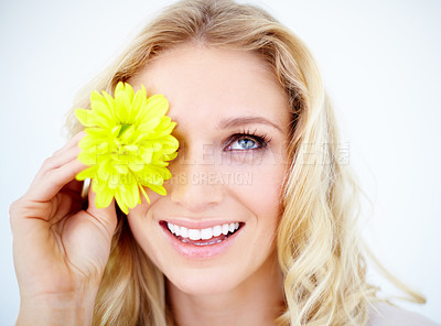 Buy stock photo Closeup of a pretty young woman covering her eye with a yellow daisy