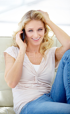 Buy stock photo Portrait of a pretty young woman taking a call while relaxed on her sofa