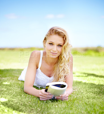 Buy stock photo Portrait of a pretty young woman reading a book while in her garden
