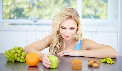 Buy stock photo Pretty young woman being tempted to eat unhealthy food
