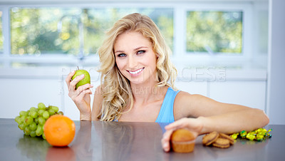 Buy stock photo Pretty young woman choosing a healthy apple over junk food