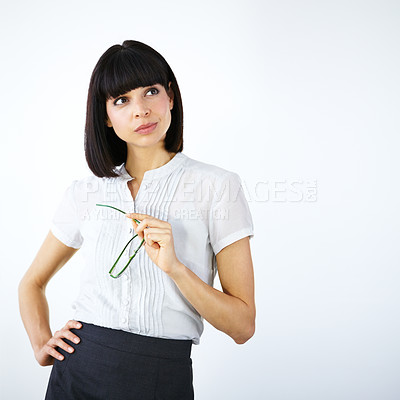 Buy stock photo A businesswoman holding glasses and looking towards copyspace thoughtfully