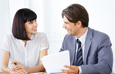 Buy stock photo Two young executives enjoying a conversation in the office together