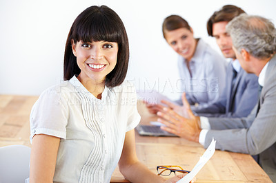 Buy stock photo Portrait of a pretty young executive at a strategy meeting with her business team