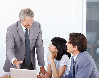 Buy stock photo A business manager advising his two younger colleagues at a meeting