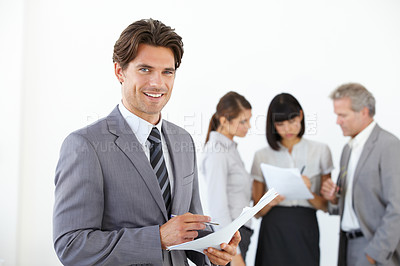 Buy stock photo A young handsome executive holding documents while his team stands in the background