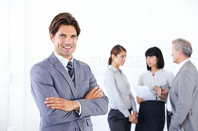 Buy stock photo Portrait of a handsome young executive standing with arms crossed while his team talks in the background