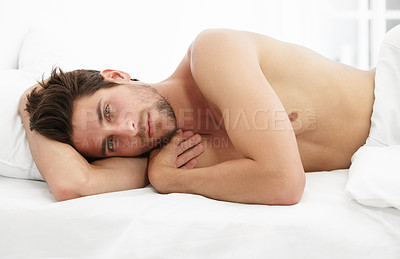 Buy stock photo Portrait of a handsome man lying comfortably in bed relaxing