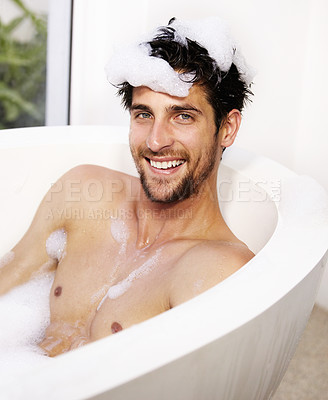 Buy stock photo Portrait of a happy man smiling with foam on his head sitting in a bath tub relaxing