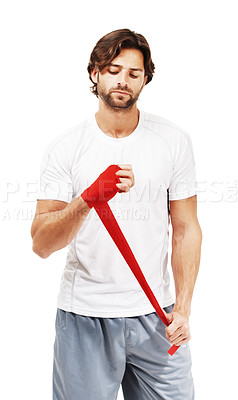 Buy stock photo Young fit male wrapping up his hand and wrist with red tape and strapping - isolated on white