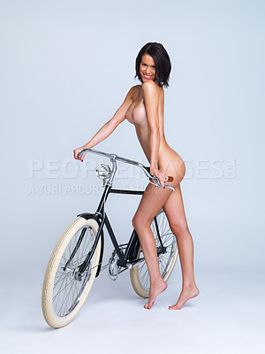 Buy stock photo Cute young nude woman standing alongside a bicycle isolated on grey
