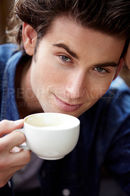 Buy stock photo A young man about to take a sip of coffee