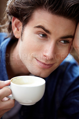 Buy stock photo A young man looking to the side holding a cup