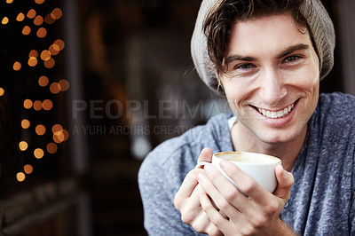 Buy stock photo A young male smiling as he holds his coffee