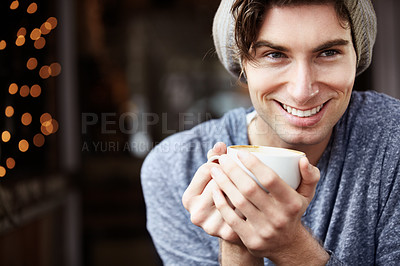 Buy stock photo A young man looking ahead as he holds his coffee