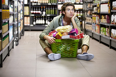 Buy stock photo A young man sitting on the floor anxiously overwhelmed by grocery shopping