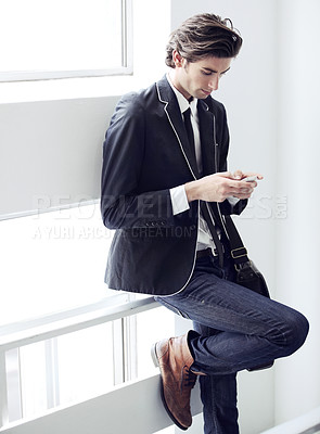 Buy stock photo A young man reading the reply he received
