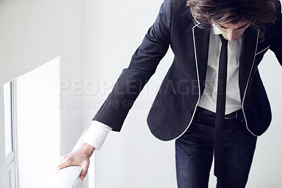 Buy stock photo A young man looking down and thinking