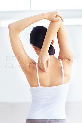 Buy stock photo Young woman stretching while indoors - rear view