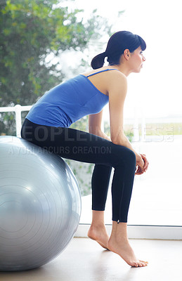 Buy stock photo Healthy young woman sitting on an exercise ball