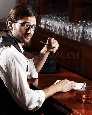 Buy stock photo Portrait of a handsome young man sitting at a bar with a pen and notebook