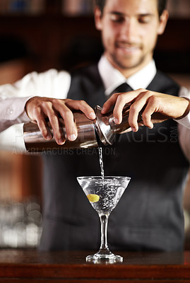 Buy stock photo Shot of a handsome young bartender mixing a cocktail