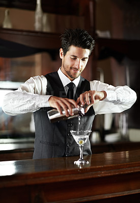 Buy stock photo A handsome young bartender mixing a cocktail for a customer