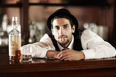 Buy stock photo Portrait of a handsome young bartender smoking with a bottle of whiskey next to him