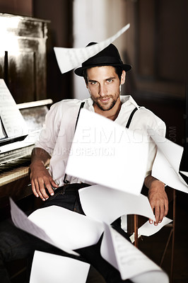 Buy stock photo Portrait of a handsome young musician sitting at a piano with sheet music falling all around him